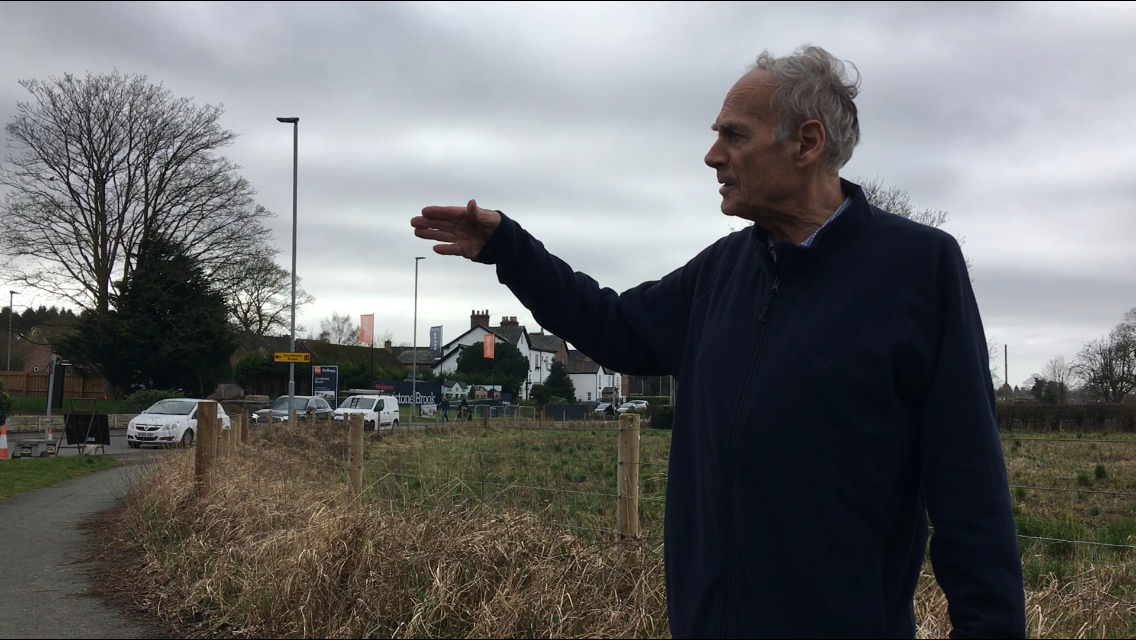 Cllr Ian Marks pointing towards traffic on Rushgreen Road